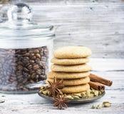 Hemlagade wienerbrödkakor som smaksättas med kardemumman och den kanel staplade högen som förbi omges, kryddar en krus av kaffe Royaltyfri Bild