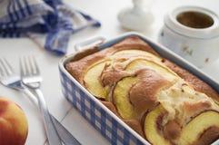 Hemlagat banta sockerkakan med nektariner i blå keramisk maträtt Royaltyfri Bild