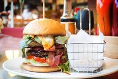 Hemlagat bbq-griskött med bacon- och osthamburgaren Tjänat som med den stekte fransmannen Arkivfoto