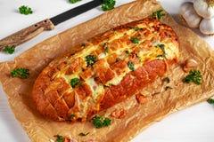 Hemlagat bröd för ostvitlökhandtag ifrån varandra med örter på skrynkligt papper Arkivbild