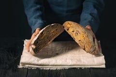 Hemlagat bröd i händerna Bröd delas in i två delar royaltyfria bilder