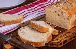 Hemlagat bröd med den solrosfrö, skärbrädan och kniven royaltyfri fotografi