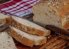 Hemlagat bröd med den solrosfrö, skärbrädan och kniven arkivbild