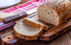 Hemlagat bröd med den solrosfrö, skärbrädan och kniven arkivbilder