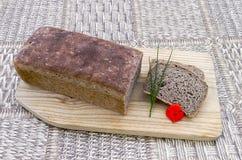 Hemlagat bröd med gräslökar och den röda blomman Royaltyfri Foto