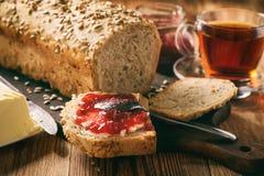 Hemlagat bröd släntrar med solrosfrö på träbakgrund arkivfoton