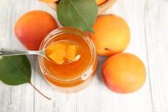 Hemlagat driftstopp för aprikos i krus med skeden och mogen saftig frukt fotografering för bildbyråer