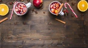 Hemlagat funderat vin med äpplet, apelsinen, kanel, kryddnejlikor och andra ingredienser har lagts ut runt om en trälantlig backg Arkivfoto
