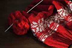 Hemlagat handarbete från röd och vit ull med stickor Närbild arkivfoto