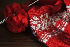 Hemlagat handarbete från röd och vit ull med stickor Närbild arkivfoton