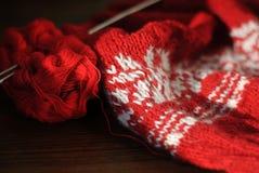 Hemlagat handarbete från röd och vit ull med stickor Närbild royaltyfri fotografi