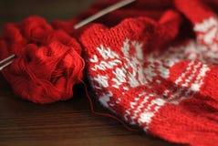 Hemlagat handarbete från röd och vit ull med stickor Närbild royaltyfri bild