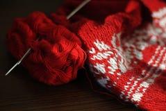 Hemlagat handarbete från röd och vit ull med stickor Närbild arkivbild