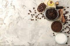 Hemlagat kaffe skurar i en krus för framsidan och kroppen, och olika ingredienser för framställning skurar på en ljus bakgrund Sp royaltyfri foto