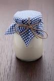 Hemlagat mjölka yoghurten i den glass krukan på trä bordlägger Royaltyfri Foto