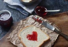 Hemlagat rostat bröd med jordgubbedriftstopp i form av hjärta, valentindagfrukost Royaltyfria Foton