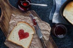 Hemlagat rostat bröd med jordgubbedriftstopp i form av hjärta, valentindagfrukost Royaltyfri Bild