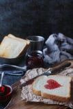 Hemlagat rostat bröd med jordgubbedriftstopp i form av hjärta, valentindagfrukost Royaltyfria Bilder