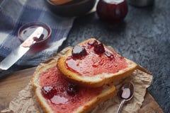 Hemlagat rostat bröd med jordgubbedriftstopp på träbrädet, läcker frukost Royaltyfri Fotografi