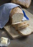 Hemlagat skivat helt kornbröd täckte med en handduk, skärbrädan, smör royaltyfria bilder