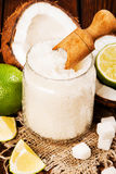 Hemlagat socker skurar med limefrukt och kokosnöten på träbakgrund royaltyfria foton