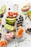 Hemlagat sommarrostat bröd med gräddost rökte lax-, blåbär-, rädisa-, gurka-, avokado- och kryddkrassesallad nytt royaltyfria foton