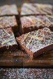 Hemlagat stycke för kaka för nisse för chokladkikärtstrikt vegetarian som lagar mat med skeden av smältt choklad på mörk bakgrund royaltyfria foton
