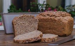 Hemlagat svart bröd med någon brödskivor och kniv som ligger på träyttersida Arkivfoto
