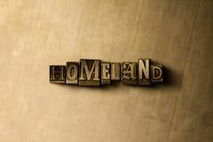 HEMLAND - närbild av det typsatta ordet för grungy tappning på metallbakgrunden royaltyfri bild