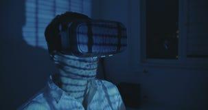 Hemlet d'uso di realtà virtuale del programmatore futuristico dell'uomo o vetri di VR con la riflessione di codice binario video d archivio
