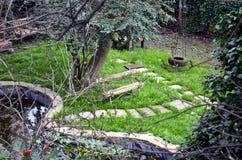 Hemlig engelskaträdgård med en bänk Arkivfoton