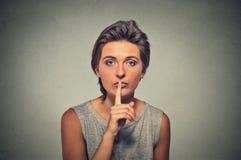 hemlig kvinna Ungt kvinnligt tecken för visninghandtystnad som frågar att hålla det tyst Royaltyfri Foto