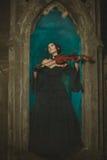 Hemlig medeltida flicka som spelar fiolen på natten Arkivbild