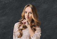 hemlighet Hyssjar det satta fingret för den unga kvinnan på kanter, tecknet Royaltyfri Bild