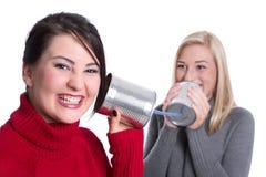 Hemligheter under flickvänner - två flickor talar tillsammans och har gyckel Arkivfoton