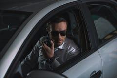 hemligt manligt medel i solglasögon som gör bevakning och använder talkiewalkie arkivbild