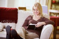 Hemma: Den nätta kvinnan skriver i personlig dagbok Royaltyfria Bilder