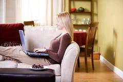 Hemma: Kvinnan skriver meddelandet på bärbara datorn Arkivbild