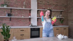 Hemmafru i grov bomullstvilloveraller och handskar med trasan och rengörande sprej i händer som poserar för kamera på kök