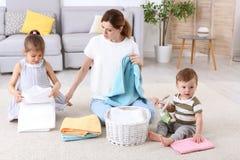 Hemmafru med barn som viker nytt tvättade handdukar royaltyfri foto