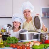 Hemmafru och dotter med crockpot på kök Arkivbilder