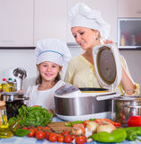 Hemmafru och dotter med crockpot på kök Arkivfoton