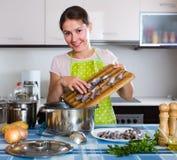 Hemmafru som försöker nytt recept av sprattusen i kök Arkivfoto