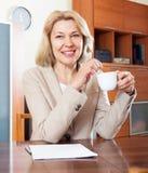 Hemmafru som i regeringsställning arbetar med dokument på inre för tabell Arkivfoto