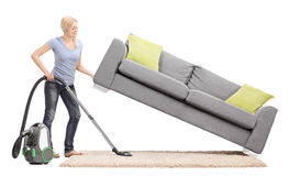 Hemmafru som lyfter en soffa och dammsuger under den Fotografering för Bildbyråer