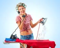 Hemmafru som talar på telefonen, medan stryka arkivfoto