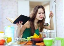 Hemmafrumatlagning med ladlen och kokbok royaltyfri fotografi