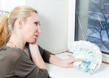 Hemmafrun gråter och räknar pengar för reparation av ett dubbelt glasat fönster Arkivfoton