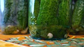 Hemmafrun häller den varma marinaden in i en glass krus med gurkor lager videofilmer