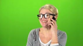 Hemmafrun i exponeringsglas talar på telefonen grön skärm arkivfilmer